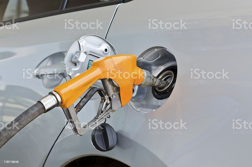 grey car at gas station being filled with fuel stock photo