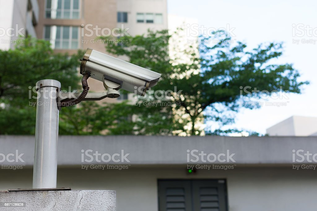 Grey CCTV camera mounted on top of a wall watching over an area. stock photo