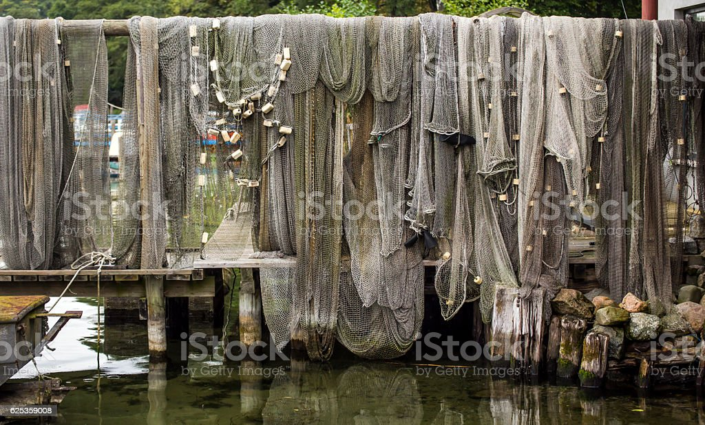 grey fishnets on a landing stage stock photo