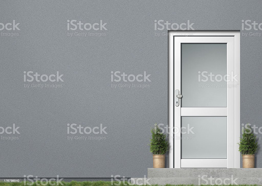 Grey house wall and white door royalty-free stock photo