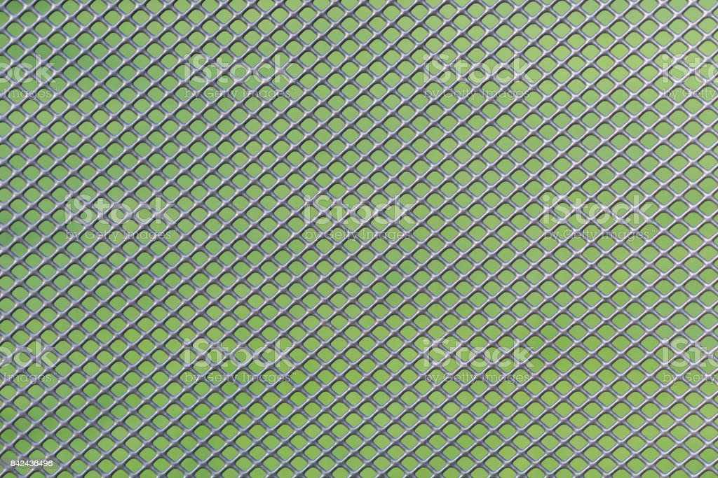 Grey metal wire mesh work against a green background stock photo