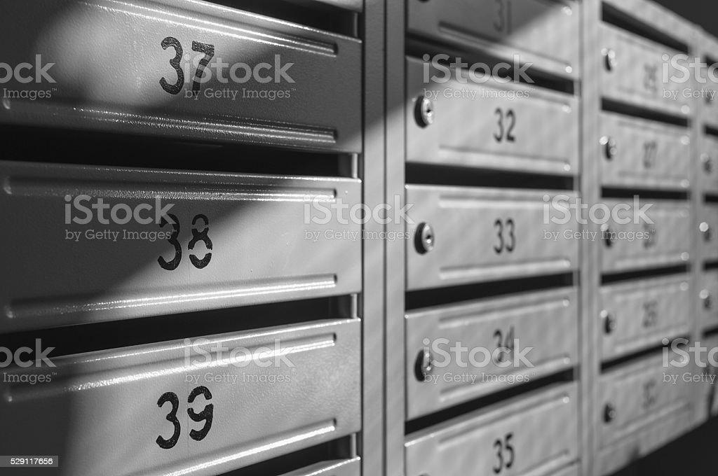 grey metallic mailbox array inside apartment houses stock photo