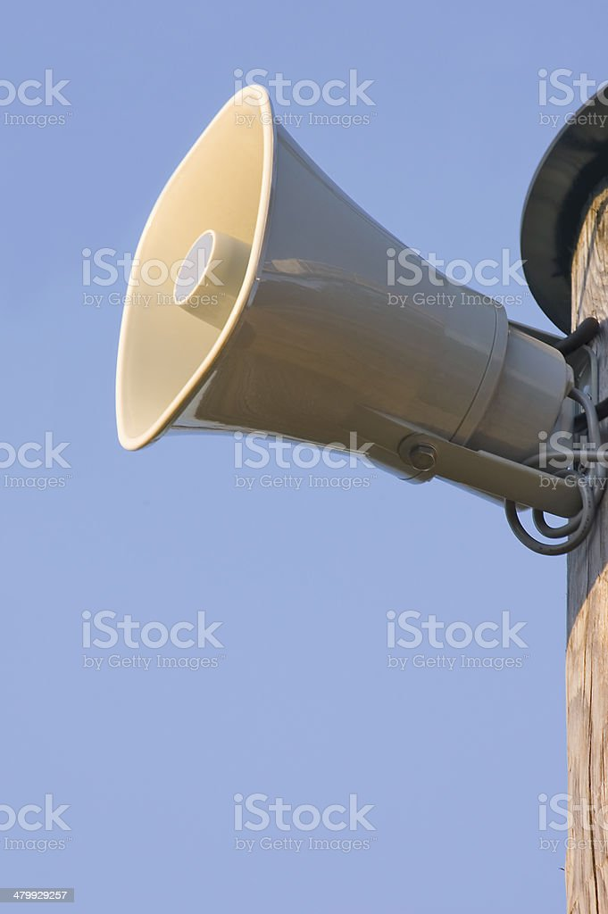 Grey plastic horn loudspeaker wooden pole, over clear blue sky royalty-free stock photo