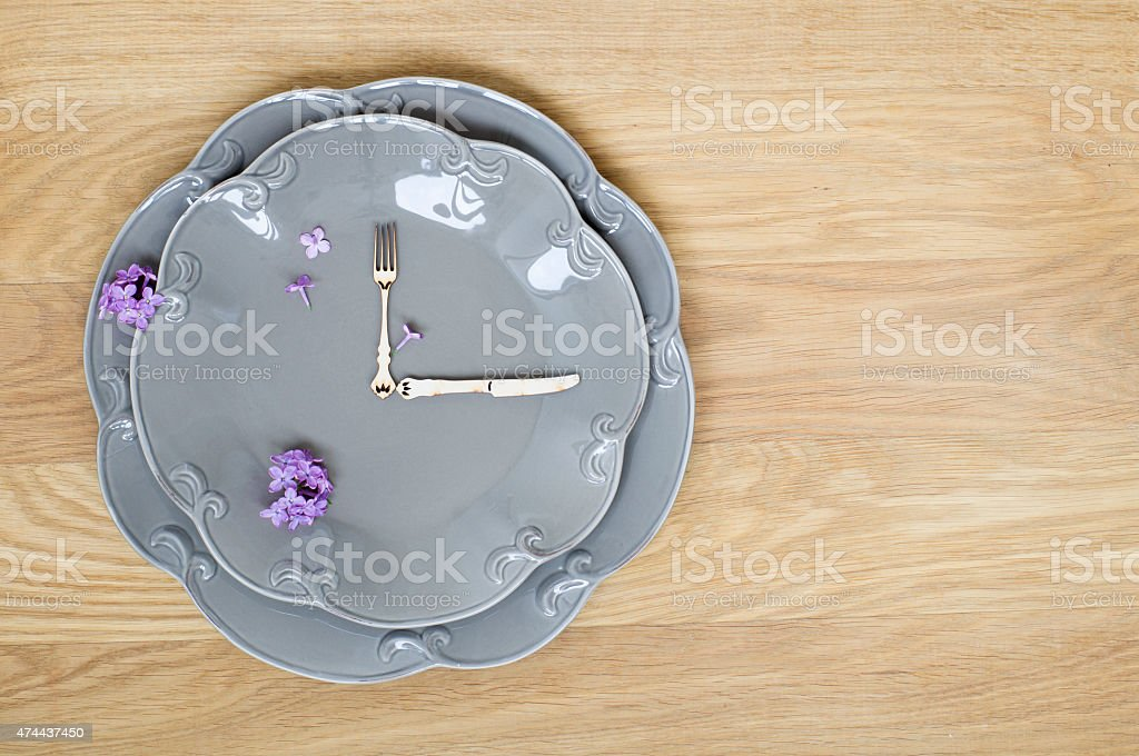 Grey plate clock on a wooden background stock photo