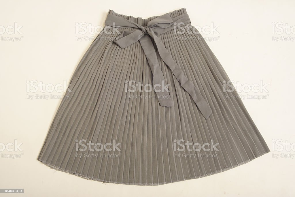 Grey pleated skirt spread out on a neutral background stock photo