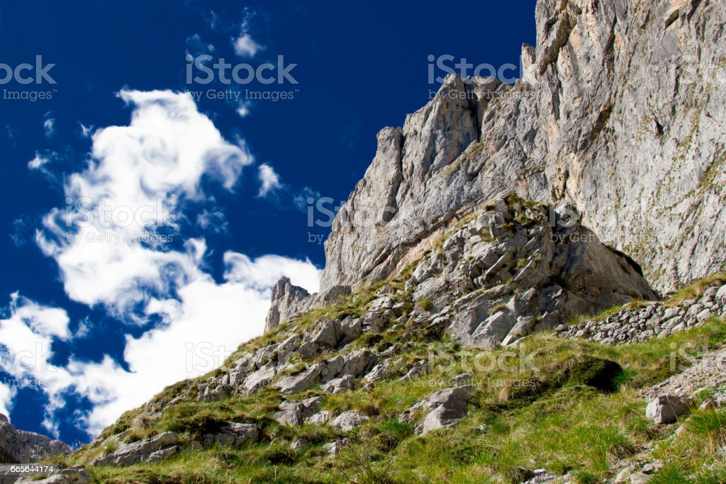 Grey rock, mountains on daytime with green grass against bright blue sky with white clouds going up, background, Spain, Picos de Europa. Perfect for extreme sport equipment, outdoor advertising stock photo