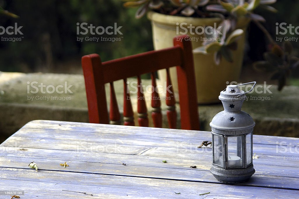 Grey table with red chair, on patio  royalty-free stock photo