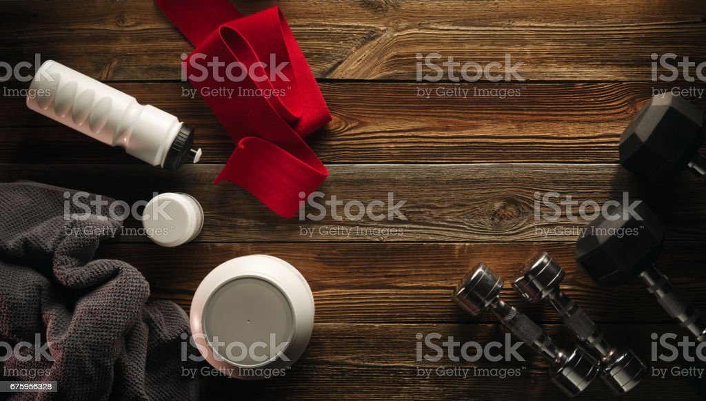 Grey towel Protein shake bottle Dumbbell plate White jar with whey protein Red hand wrap Sneakers on wooden floor stock photo