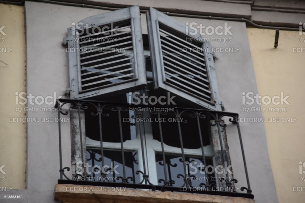 Grey wooden shutter partially opened stock photo