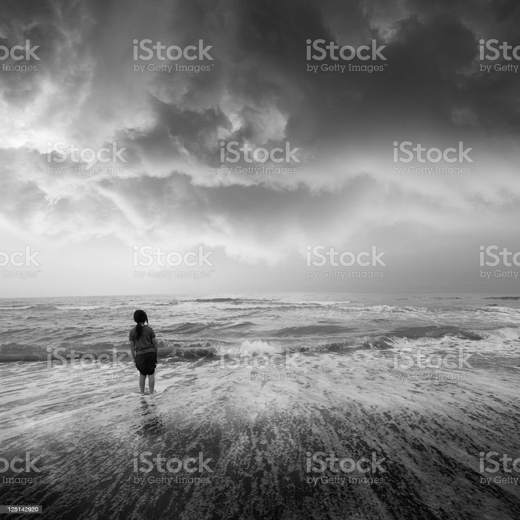 Greyscale beach landscape with young woman standing in waves stock photo
