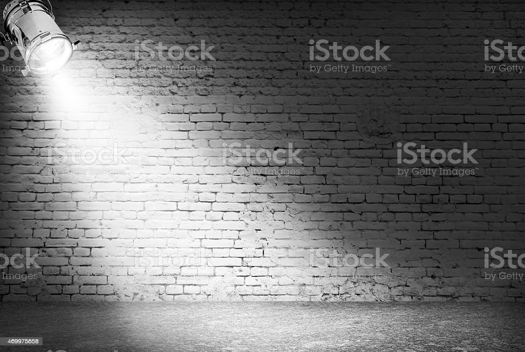 Greyscale brick wall illuminated by a corner spotlight stock photo