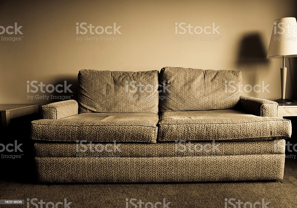 Greyscale old worn out hotel sofa in retro pattern stock photo