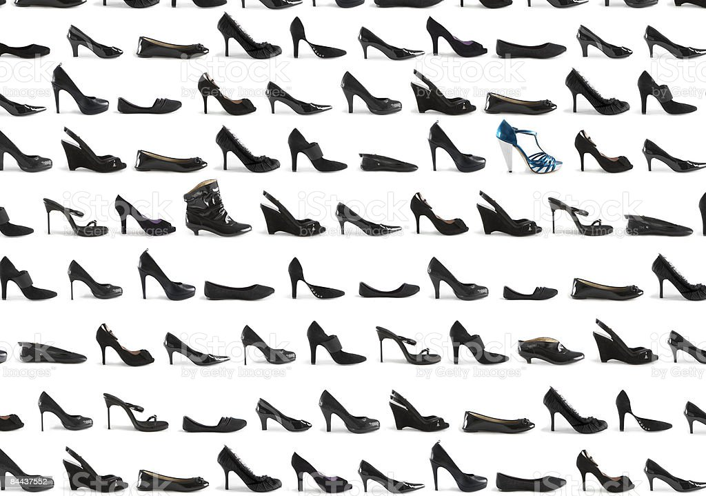 A grid of many black shoes and one blue shoe stock photo