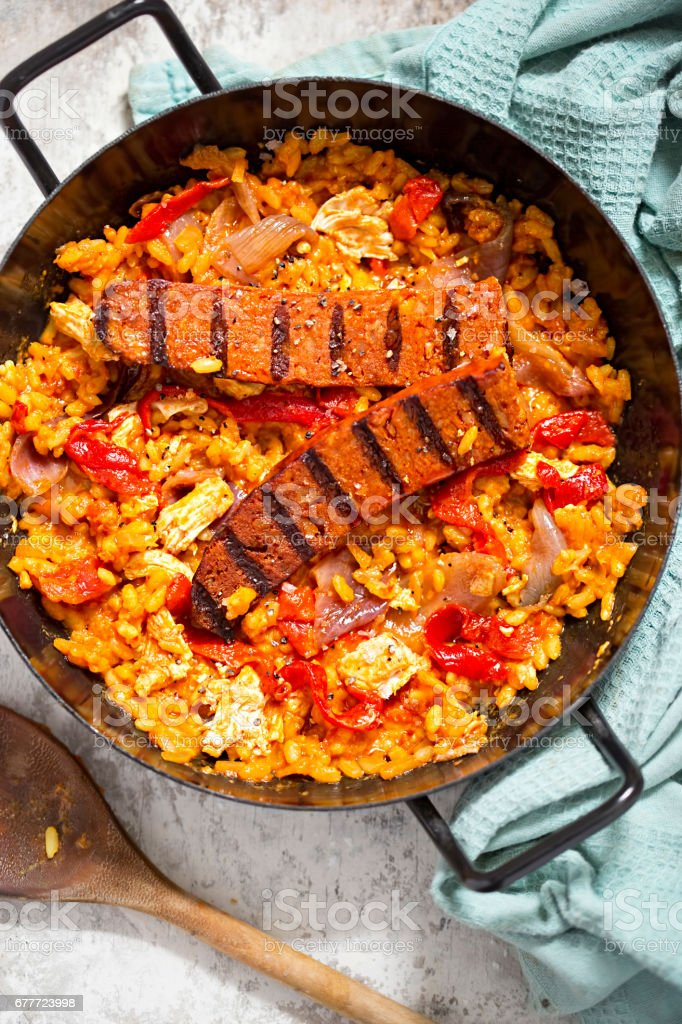 Griddled chorizo and chicken with red pepper paella stock photo