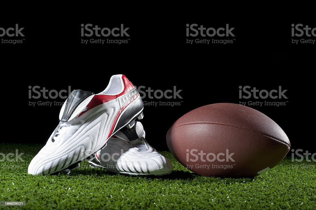 Gridiron ball and boots on grass stock photo