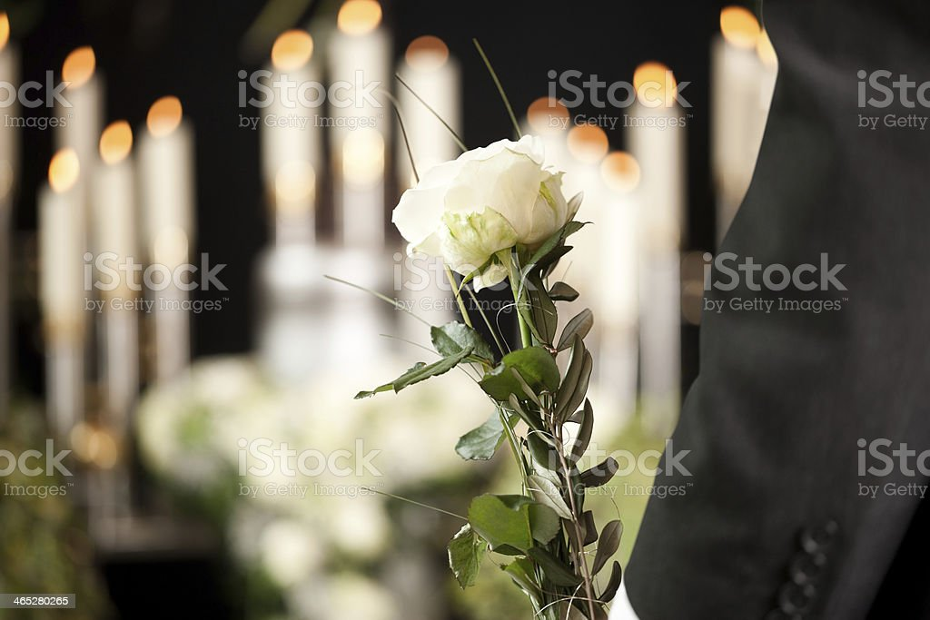 Grief - man with white roses at urn funeral stock photo