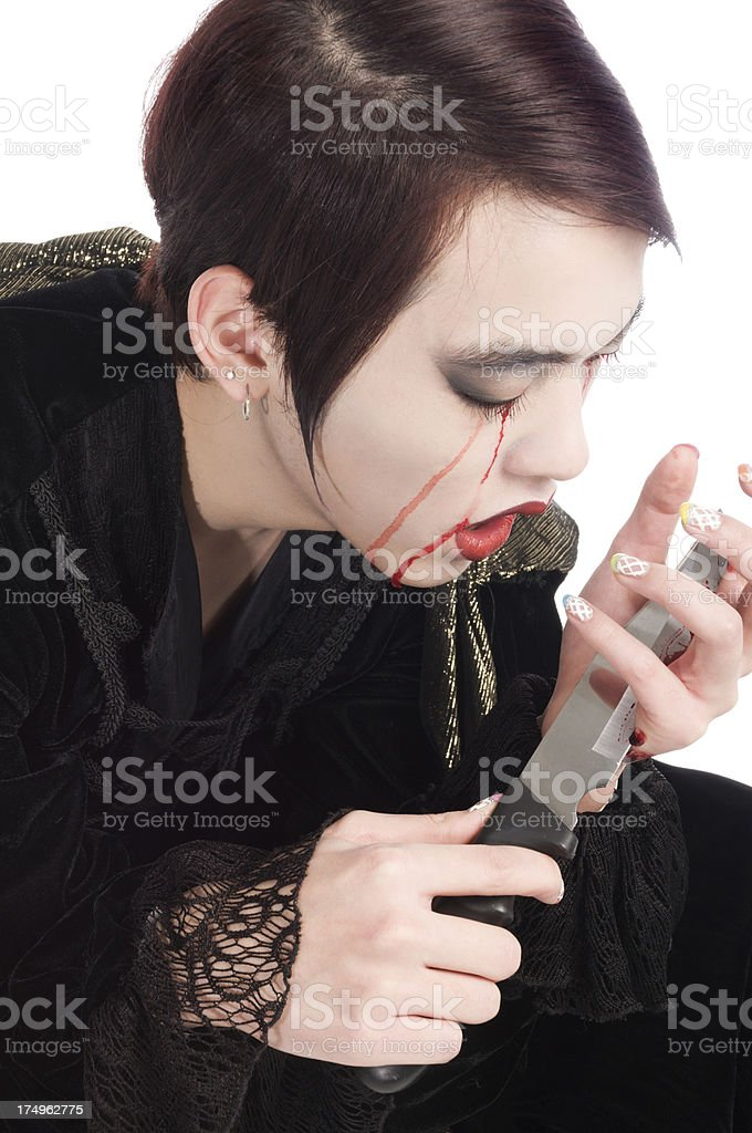 Grief stricken vampire cutting hand with knife royalty-free stock photo