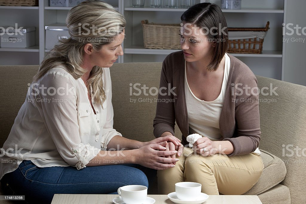 Grief Stricken Woman Being Comforted By Friend stock photo