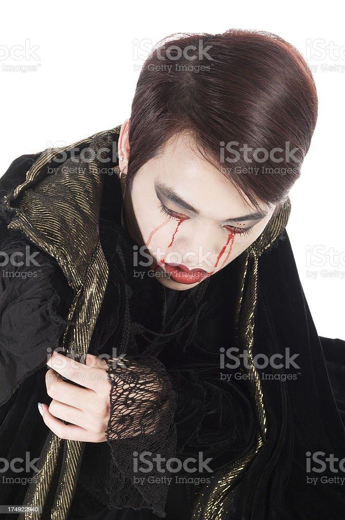 Grieving vampire huddling in velvet cloak royalty-free stock photo