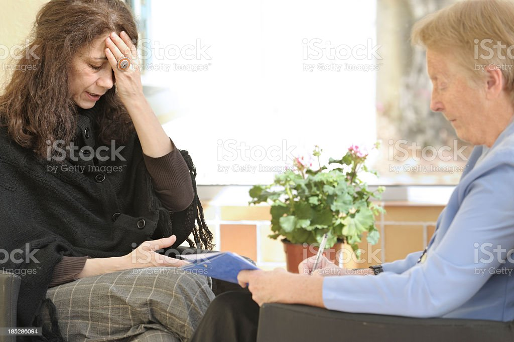 Grieving woman speaking to a therapist royalty-free stock photo