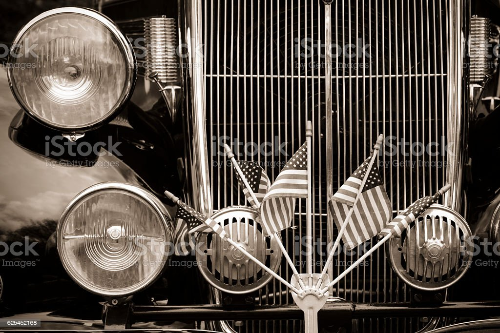 Grill of an antique car with US flags stock photo