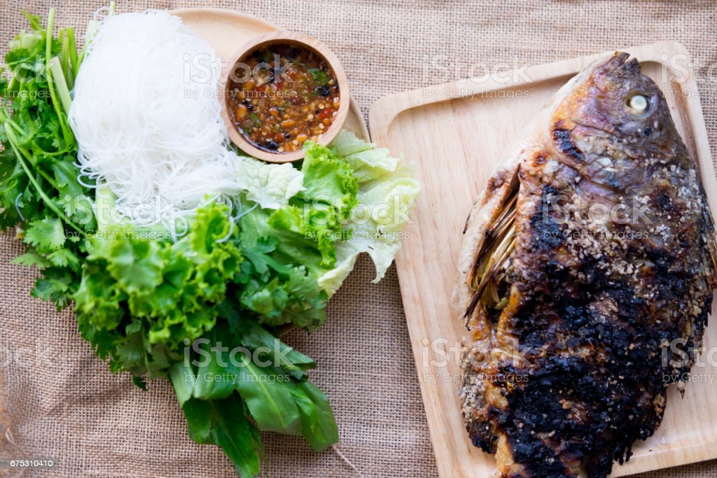 Grill salt Tilapia fish with rice noodles and spicy sauce, top view stock photo