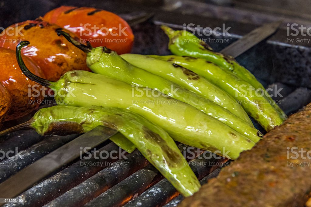 Grilled adana, tomatoes, and peppers on a Turkish restaurant grill. stock photo