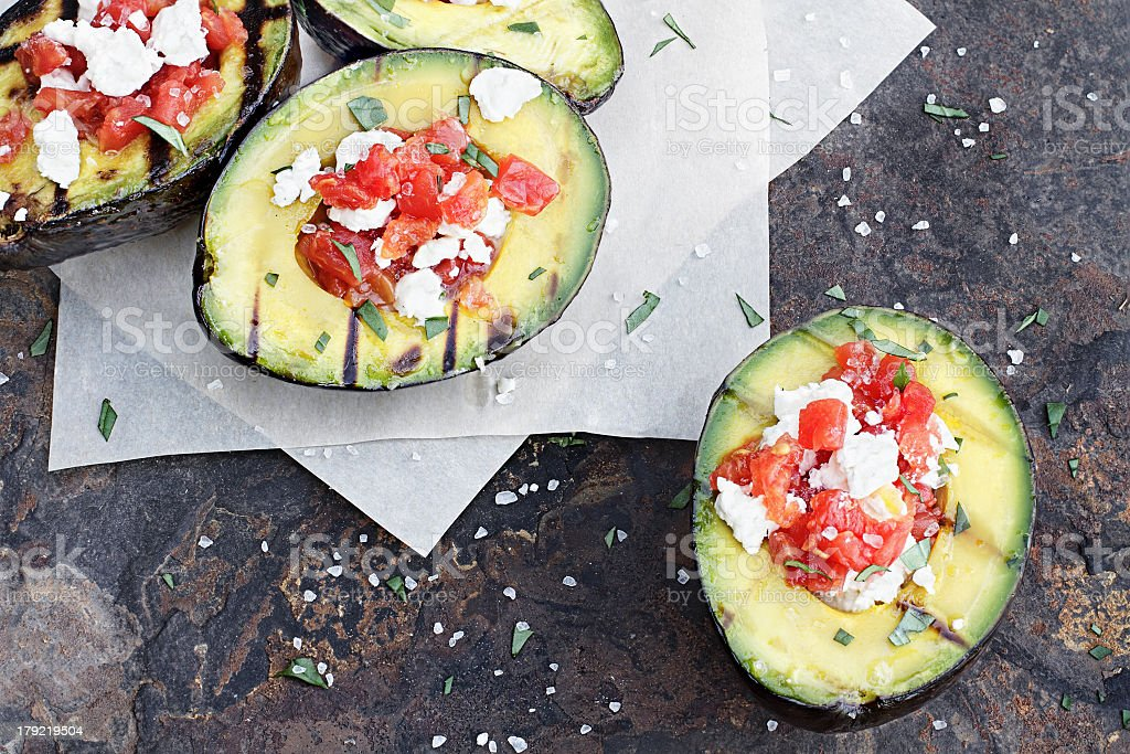 Grilled avocados filled with tomatoes and cheese stock photo