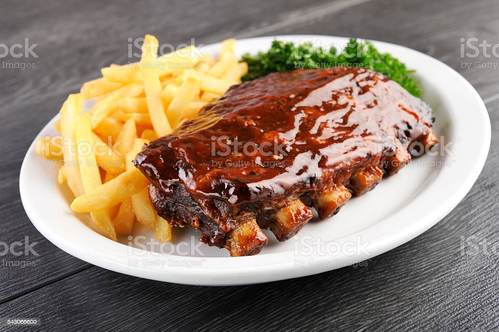 Grilled barbecue ribs and fries stock photo