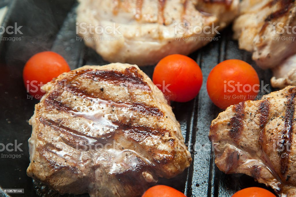 Grilled bbq steaks with fresh herbs and tomatoes stock photo