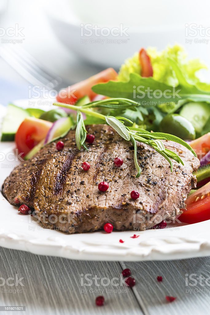 Grilled beef dish with berries and salad on a white plate royalty-free stock photo