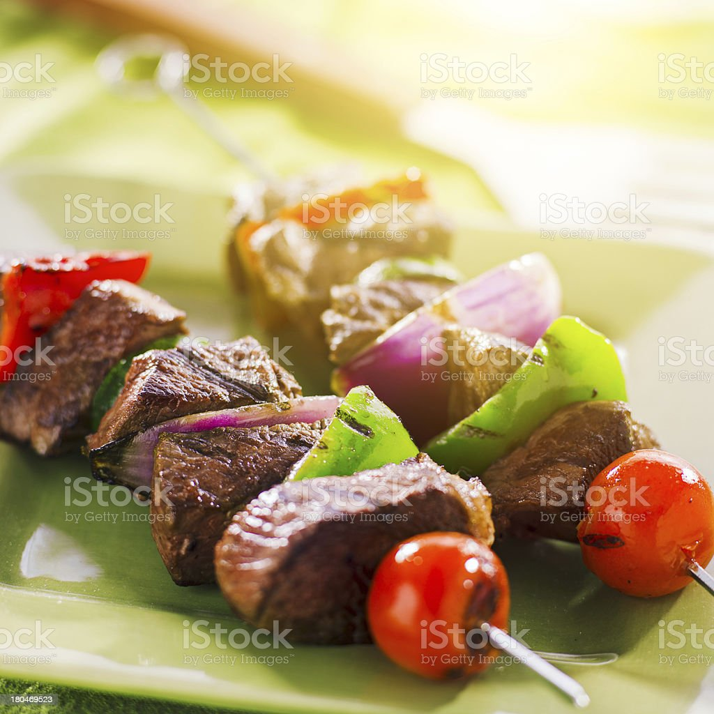 grilled beef shishkabobs on green plate stock photo