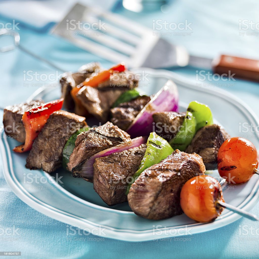 Grilled beef shish-kabobs with vegetables on a blue table royalty-free stock photo