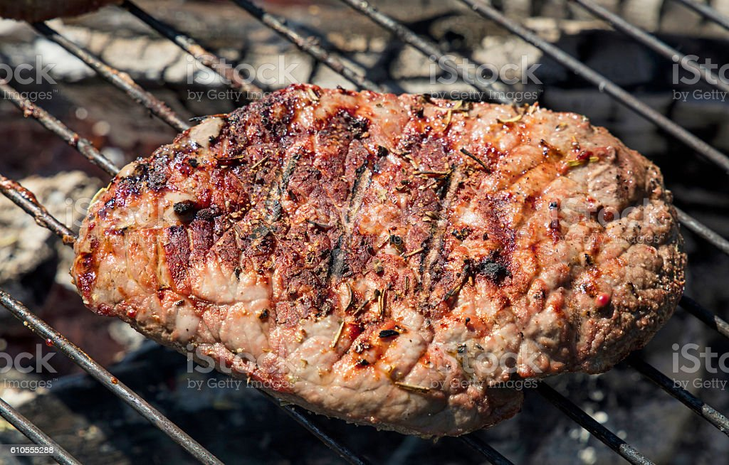 Grilled beef steak cooking on barbecue grill stock photo