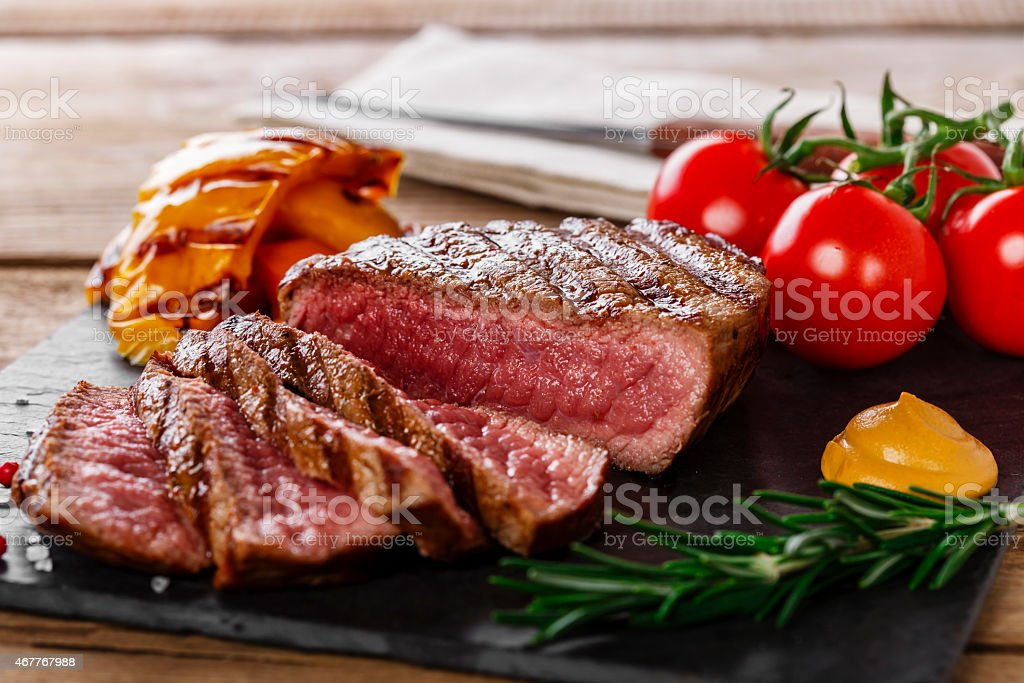 grilled beef steak rare sliced with vegetables stock photo