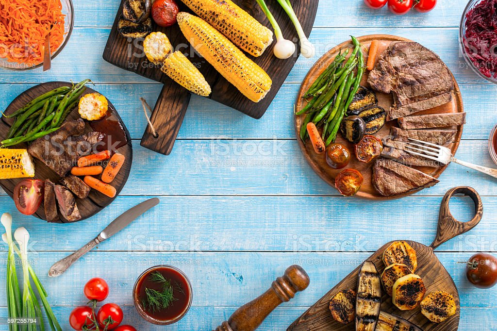 Grilled beef steak with grilled vegetables on wooden blue table stock photo
