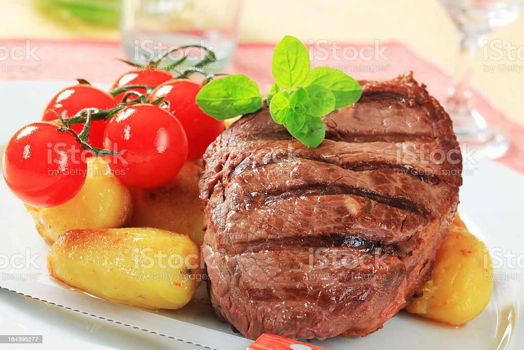 Grilled beef steak with potatoes and tomatoes royalty-free stock photo