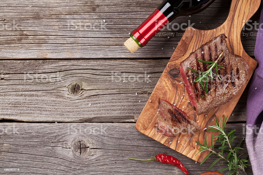 Grilled beef steak with rosemary, salt and pepper and wine stock photo