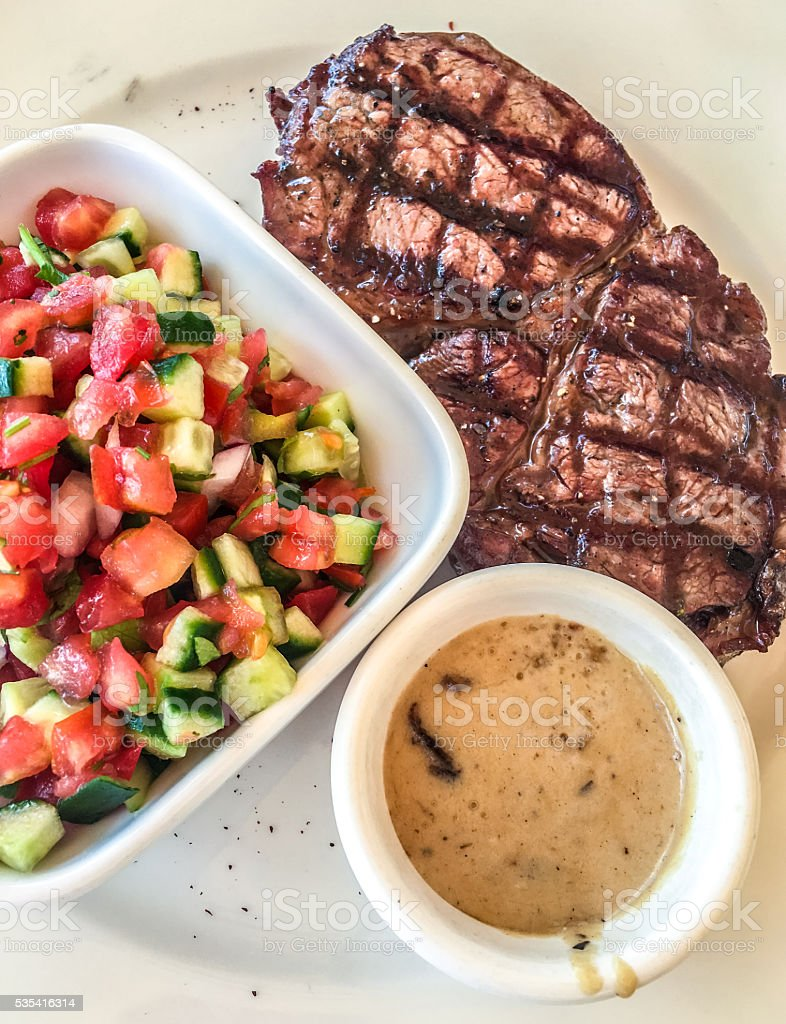 Grilled beef steak with salad and pepper sauce stock photo