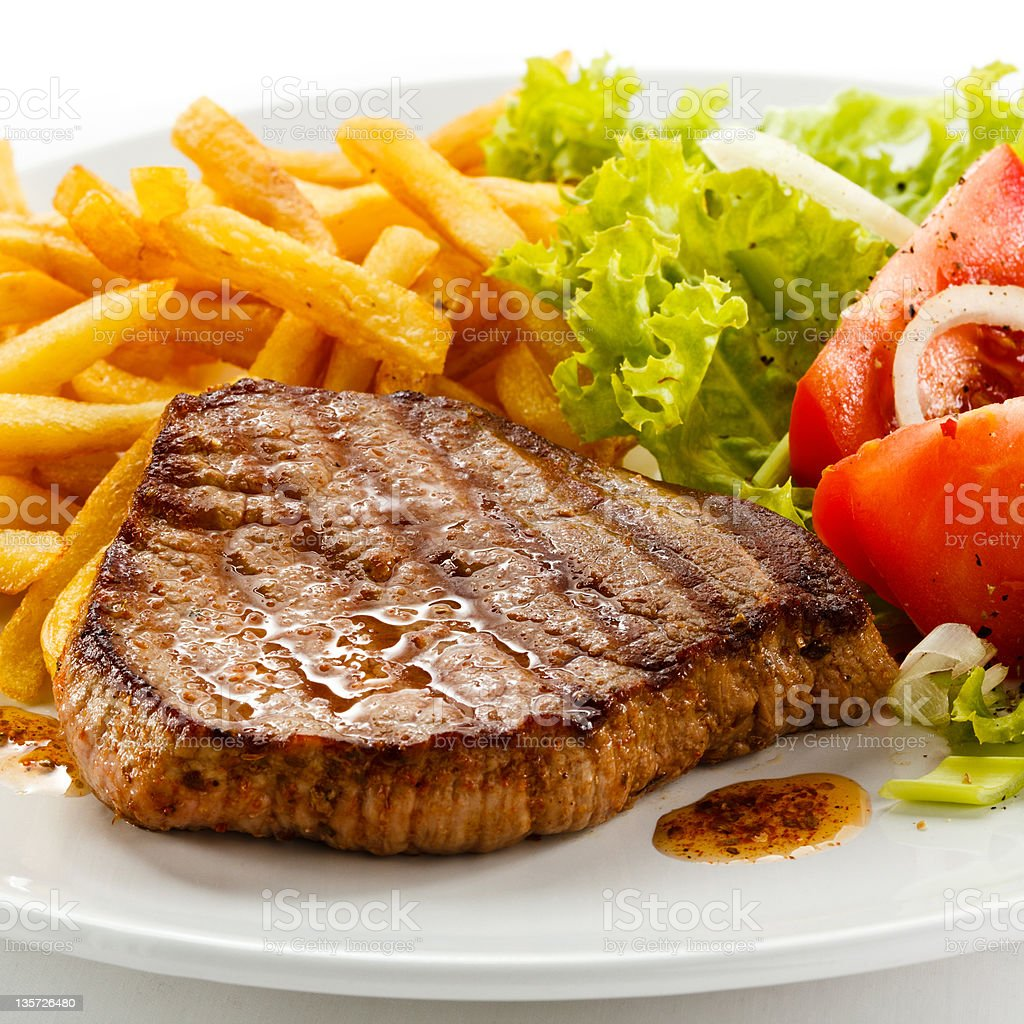Grilled beefsteak French fries and vegetables stock photo