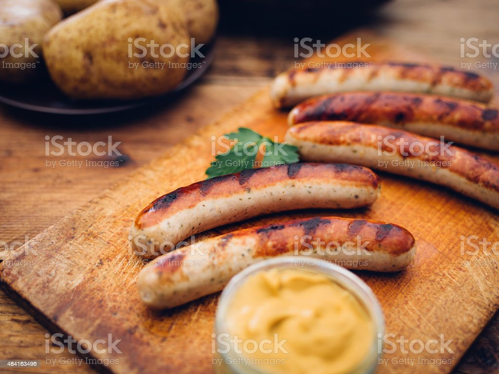Grilled bratwurst sausages with hot mustard on vintage wooden board stock photo