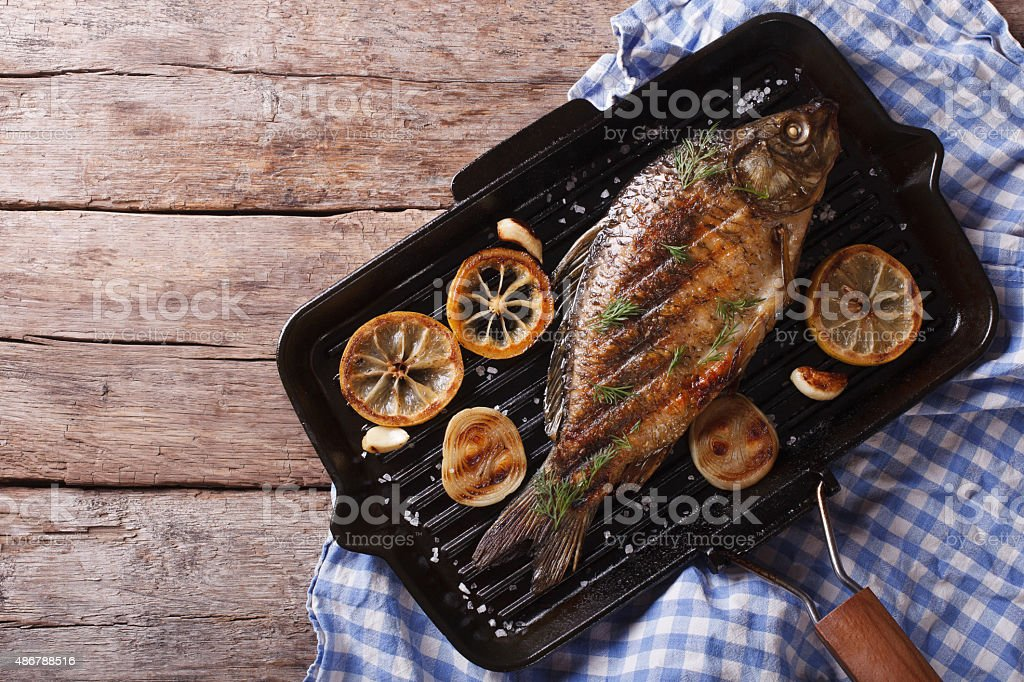 Grilled carp with lemon in grill pan , horizontal top view stock photo