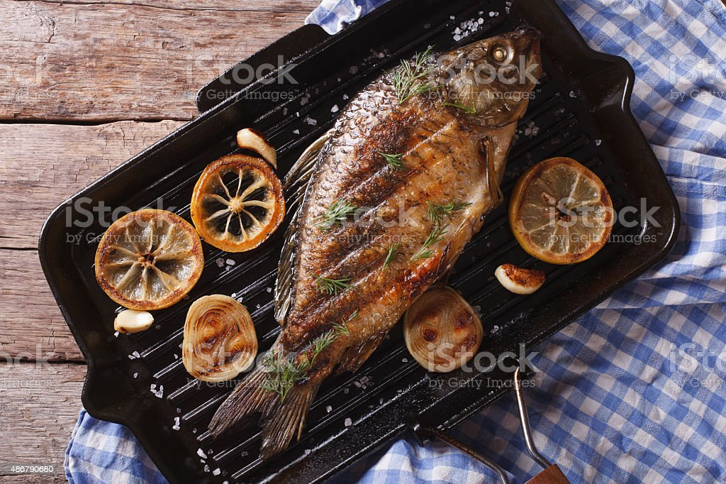 Grilled carp with lemon in pan , horizontal top view closeup stock photo