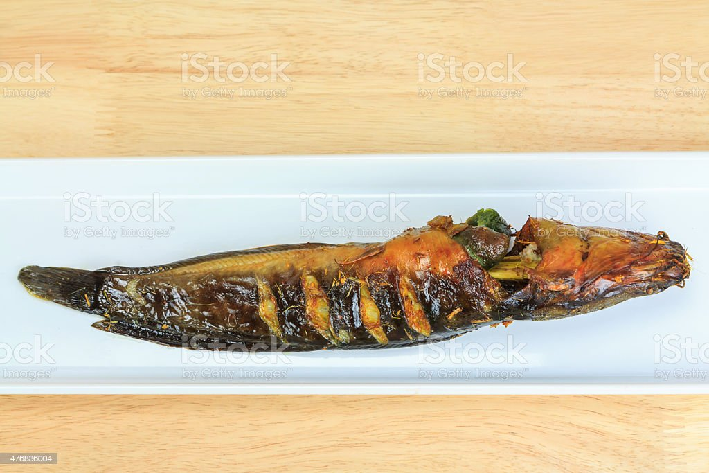 Grilled catfish and gridiron on wooden background royalty-free stock photo