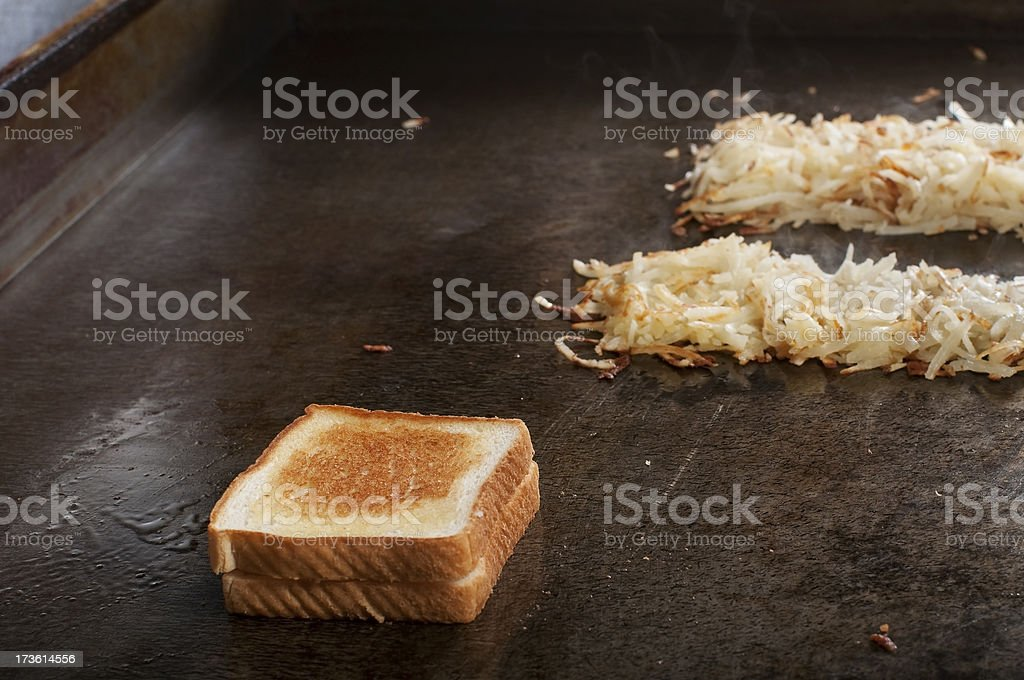 Grilled cheese and hash browns on a griddle royalty-free stock photo