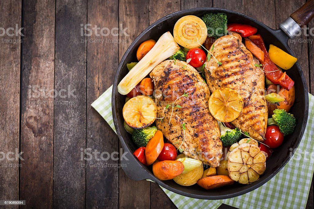 Grilled chicken breast and vegetables in the pan stock photo