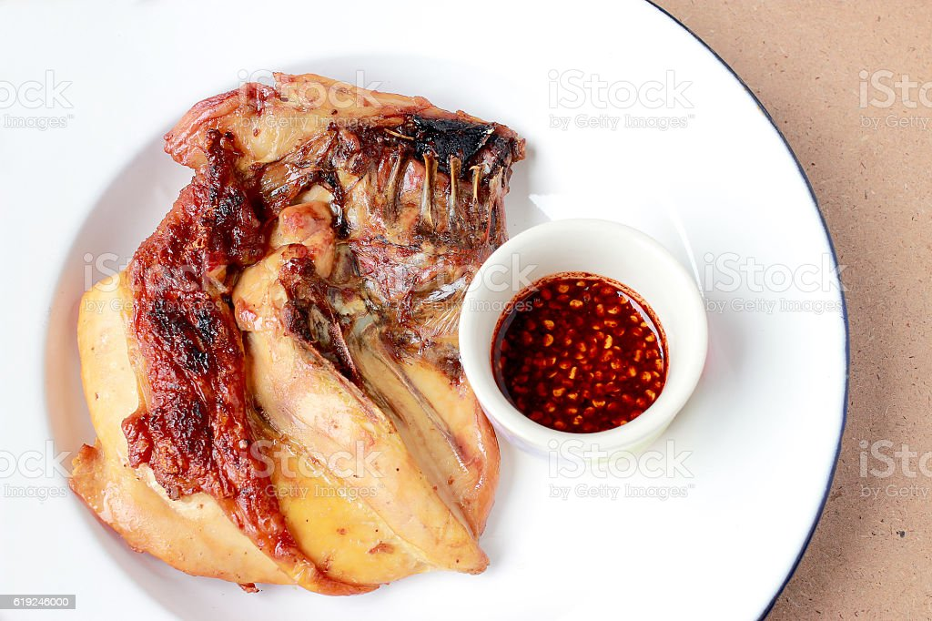Grilled chicken breast in white dish on wooden table stock photo