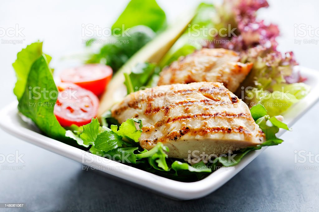Grilled chicken breast on green salad stock photo