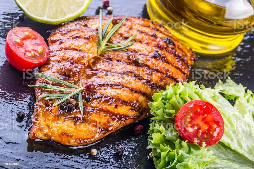 Grilled chicken breast on slate board with salad stock photo