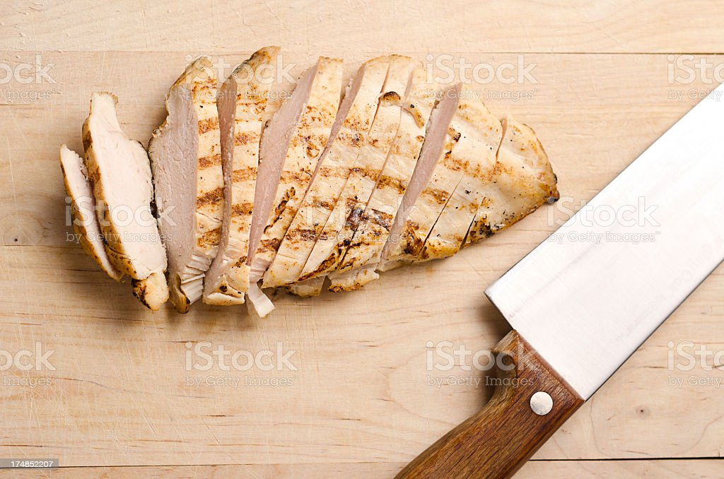 Grilled chicken breast slices on wood stock photo